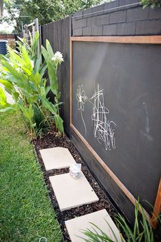 A fun DIY project for the kids! Build a frame, then buy some plastic backing from hardware store and paint it with chalk board paint. After your done hang it on the fence and let the kids have at it!