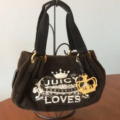 """Juicy Couture handbag Brown Terry fabric with beige embroidery. Gold tone D rings hold the Brown cotton handle with leather grips.Golden heart charm hangs on the right of the logo embroidery. Back has large leather heart with a J sewed in. Magnet closure and strap/buckle interior closure too. 2 interior pockets , 2 small magnet closure pockets on each side. - Length 12 x width 6 x height 7 inches handle drop is 7"""" some wear on the bottom of bag, tiny scratch on leather piping. Main leather…"""