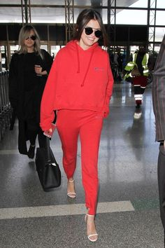Selena Gomez paired a red hoodie with matching sweats, adding heels for a chic twist.