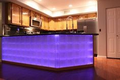 This glass block bar really has some punch with LED lights behind it. Makes a cool counter and breakfast bar in this kitchen. #LED #kitchenbar http://innovatebuildingsolutions.com/products/glass-block/glass-block-walls-bars