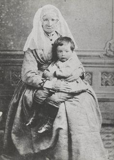 Vrouw (geb. 1828) uit de omgeving van Heerjansdam, gekleed in de streekdracht van de Zuid-Hollandse eilanden. Op haar schoot zit een kind in modekleding. ca 1860 #IJsselmonde #ZuidHolland
