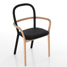 """Presented for Italian brand Porro in Milan last week, the Gentle chair has a matching black leather seat but pale wooden front legs, which continue up and around the backrest in one loop to form arms."""