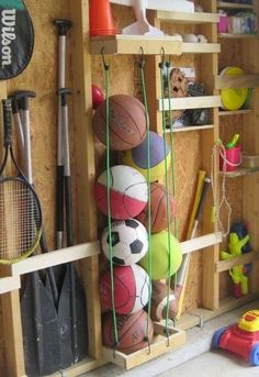 Bungee cord ball storage makes different balls easy to access and find. Horizontal slats store tall items and plenty of shelves hold onto other toys. A tennis racket gets it's own space using two nails to support either side of the handle and it lays flat against the wall.