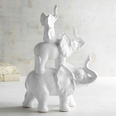 "Our playful pachyderm family will have you rethinking the term ""white elephant"" from now on. Everyone knows trunks up mean good luck, so—should your favorable fortune increase threefold once you take these ceramic cuties home—you'll know whom to thank."