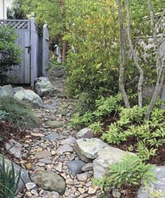 garden paths A gently meandering path offers planting pockets. Even in this narrow side yard, there is room for a few small shrubs and trees. Landscaping With Rocks, Backyard Landscaping, Landscaping Ideas, Dry Riverbed Landscaping, Inexpensive Landscaping, Side Garden, Garden Paths, Rock Garden Borders, Small Shrubs