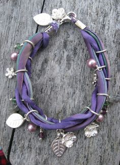 Purple and abalone-dyed silk cords, silver charms, Swarovski pearls and crystals, and labradorite disks.