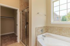 First floor master bathroom with tiled standup shower and soaking tub in the Potter Craftsman KS