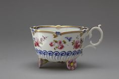 H. & R. Daniel Bone China Cup (1828-1830) painted with applied relief decoration. Supported on three pink flowers applied in relief. The lower part has a row of scrolls in relief and painted over in enamel blue.