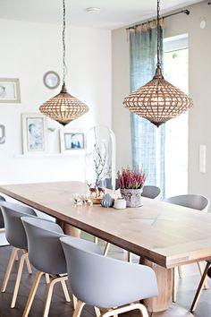 Esszimmer mit grauen Design-Stühlen und zwei interessanten Pendelleuchten