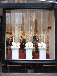 Christmas Window Display.  Love the simplicity of just white branches framed by the simple sheer drapery