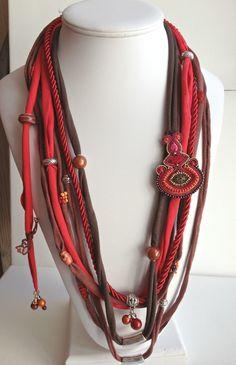 <p>Sautoir multi-liens de jersey recyclé, cordelette de fils, perles de verre, résine, bois, métal ciselé, soutache, dentelle, rocaille, l'ensemble cousu ou enfilé sur les liens de jersey.</p> <p>Longueur 42 cm.<br />A porter sur une tunique ou un pull et vous voilà parée !<br />Très agréable à porter, on ne le sent pas !</p> <p></p> <p></p>
