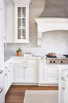 White and gray kitchen features a zinc French kitchen hood with corbels stands over a gray mini subway tile backsplash and an integrated stainless steel stove with pot and pan drawers below.