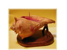 Conch Shell Candles. Make a stand for the shell with stained and sealed wood, then fill shell with several different layers of colored and scented waxes with a wick.