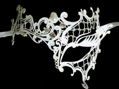 """This Venetian Filigree masquerade mask is excitingly different having an asymmetric style of scrolling decoration to enhance your face. The eye is accentuated by the lash detail. This fabulous pure white metal mask is exquisitely decorated by hand in Venice to traditional methods with faux pearls and genuine Swarovski crystals.... As seen in the movie """"Step Up 4 Miami Heat"""" This is a light and comfortable mask to wear which ties with satin ribbons."""