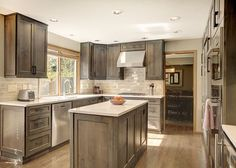 Thoughtful, handsome kitchen remodel, newly reconfigured with chef-friendly working spaces. A current, classic palette of alder gray stained cabinetry, soft white quartz countertops and hand glazed backsplash tile. High quality details in the center island, premium built-in European appliances, and LED under cabinet lighting. Construction & Design by Steven Ray Construction, Inc.