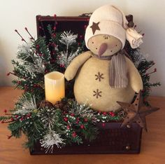 """This is a large chest measuring approximately 11""""W x 10""""D x 12""""H. The vintage snowman is sitting on a bed of Spanish moss. The chest is embellished with pine, frosted Ming pine, pip berry sprigs, faux pine sprigs, glittery leaves, assorted rusty jingle bells, a perforated """"rusty"""" star and a battery operated flicker candle. $48"""
