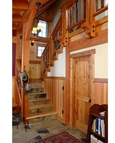 Timber frame home foyer, stone floors and stairs