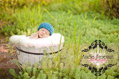 Newborn baby boy in blue bucket wearing blue beanie hat in lush greenery.  Outdoor newborn session. www.TheAthensNewbornPhotographer.com