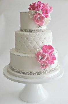 White wedding cake with bling and pink flowers