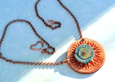 Sun Storm Leather and Star Riveted Neckace with Copper Chain by Bandana Girl  All handmade, dyed  and textured leather focal in Sun Dial theme with fringed turquoise leather, patina disc and star rivet.  Completed with 3mm copper rolo chain and handmade heart clasp in copper.   This is a great piece for the coming warmer months and will wear well!  Original designs by Melinda Orr  All jewelry designs come boxed as seen below: