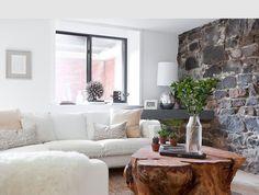 brooklyn home company den rock wall white sofa silver lamp tree trunk coffee table