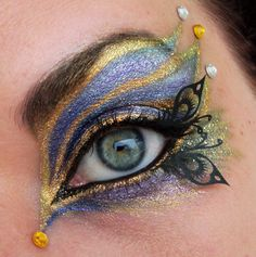 Gorgeous light blue and gold peacock inspired eye make up with little black butterfly wings and #gems #gold #blue