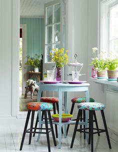 Banquetas com assento de tecidos coloridos.