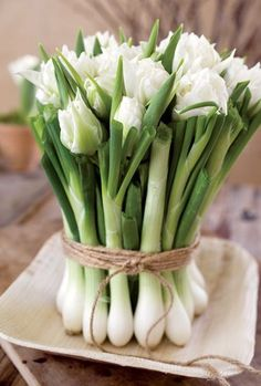 Rustic twine binds green onions and white flowers into a charming centerpiece