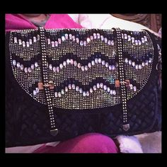 The Blazing Bling Satchel! It's a very posh bling satchel. It has blingy faceted gems in a chevron style and a sea of sparkling rhinestones. It has a cool chain strap and an attachable longer strap too. Polka dot lining inside, a zippered pocket, cell phone pockets. Under the flap are 2 zippered pockets. The top flap has magnetic closure. It's distressed denim and its vegan (faux leather) it is simply a spectacle. For that special chica that loves all that blings! Measures 15L x 9.5H x 5.5W…
