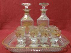 Conjunto em cristal francês Baccarat decorado em dourado, constando de 2 licoreiras, 12 copinhos e bandeja. Base R$1.540,00 (ago14).
