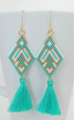 This earring design was created using brick stitch and ladder stitch to create a boho/tribal design. 6 lb. fireline was used to bead the gold, turquoise, and white miyuki 11/0 delica seed beads, so the earring shape is strong, but are almost weightless on your ear. The earring