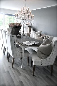 Grey rustic dining table with beautiful fabric chairs. The combination is modern and elegant.