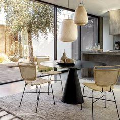 chaises en rotin AM.PM avec table ronde noire et suspension en matière naturelle pour une décoration moderne et naturelle