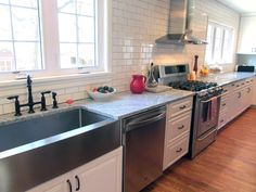 Subway tile wall, stainless steel farm sink and stainless appliances works with the 'vintage' kitchen