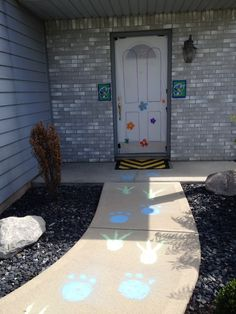 Boo's door (made from a table cloth and permanent markers) door mat (made with black and yellow duct tape and cardboard) monster foot prints with sidewalk chalk.  #monsters inc