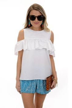 """A cute cold shoulder top with a ruffled sleeve detail in a classic white hue! Top has a button keyhole detail in the back. So cute with our """"Turquoise Palms Short."""" Fabric is a crisp cotton-blend.     Fit is true to size. Mattie is wearing size small."""