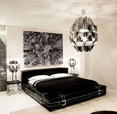 Contemporary black and white bedroom with shiny silver chandelier and painting above the headboard, which make the room look sophisticated