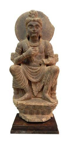 Bodhisattva assis à l'européenne sur un trône. Les mains en position «Dharmacakra-mudra», geste de l'enseignement ou de mise en route de la Roue de la loi. Il est vêtu du paridhâna et de l'uttarîya. Le premier est drapé autour de ses reins et atteint les chevilles. L'uttarîya drape légèrement son torse nu, passe sur le bras droit et s'enroule par deux fois autour de l'épaule gauche, avant de retomber jusqu'à la cheville. Il est paré de colliers, bracelets, brassard, pendants d'oreilles, ...