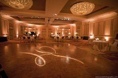 amber uplighting with a monogram on the dancefloor
