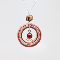 Celebrate recycled beauty with this newspaper and pink handmade paper pendant.