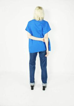 Vintage Royal Blue Box Tee ------------------------------------- Clean lines and the perfect shade of blue is what this baby has to offer. Minimalist shape with maximalist color. Drapes nicely. Short sleeve. Slips on over the head. Color: Blue Measurements: Wears as a Size L, ovesized - Collar 9 - Shoulders 24 - Sleeve 5 - Bust 48 - Waist 42 - Hips  - Inseam  - Total Length 26 Tags: 100% Polyester, Machine Washable-1, size C2, Made in USA-1 Condition: Pristine! No known flaws.  Like this…