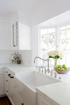 A gorgeous farmhouse sink is paired with an antique polished nickel faucet mounted in front of a bay window to a honed white marble countertop accenting white cabinets adorning oil rubbed bronze hardware.