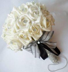 O que você acha de poder guardar o seu buquê de noiva por muito tempo? Esta é a nossa proposta na elaboração de buquês confeccionados com flores permanentes. Este branco com ponto  de luz e fitas brancas com detalhe em preto.Possui 36 botões de rosas de EVA ( similar a rosa natural). O cabo em contas prata.