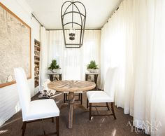 Floor-to-ceiling draperies add a sense of privacy to the light-and-bright sunroom, where built-ins hold a collection of Royal Doulton stoneware pitchers.