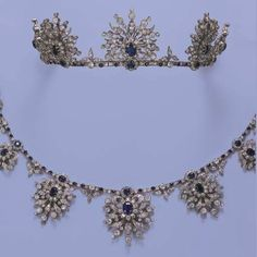 AN ANTIQUE SAPPHIRE AND DIAMOND NECKLACE/TIARA--Designed as seven graduated openwork old-cut diamond foliate motifs with oval sapphire centres, each suspended from sapphire and diamond floral clusters and collet line, all motifs detach to form brooches, with fittings for brooches and a tiara, mounted in silver and gold, circa 1880.