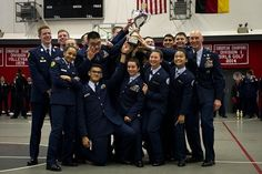 SHAPE's drill team hoists the overall team champion trophy in a group photo with Maj. Gen. Timothy Zadalis, U.S. Air Forces in Europe and Africa vice commander, right, during the DODEA-Europe JROTC drill team championships in Kaiserslautern, Germany, on Saturday, March 4, 2017. SHAPE also won seven other team and individual awards during the competition. (MICHAEL B. KELLLER/STARS AND STRIPES)