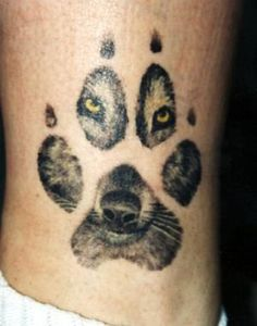 Wolf tattoo with wolf looking through paw print.