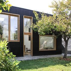 Pale wooden window frames contrast with the black stained cedar facades of this extension to a detached house in Nantes by Bertin Bichet Architectes.