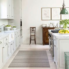Bright, white kitchen with green lights and pops of color. | See this Instagram photo by @loithai