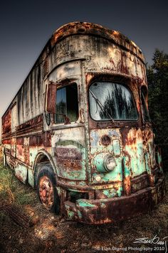 A very old and rusty RV sits in a salvage yard in Texas.